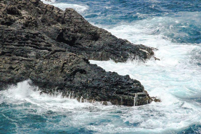 High Angle View Of Waves Crashing Rock