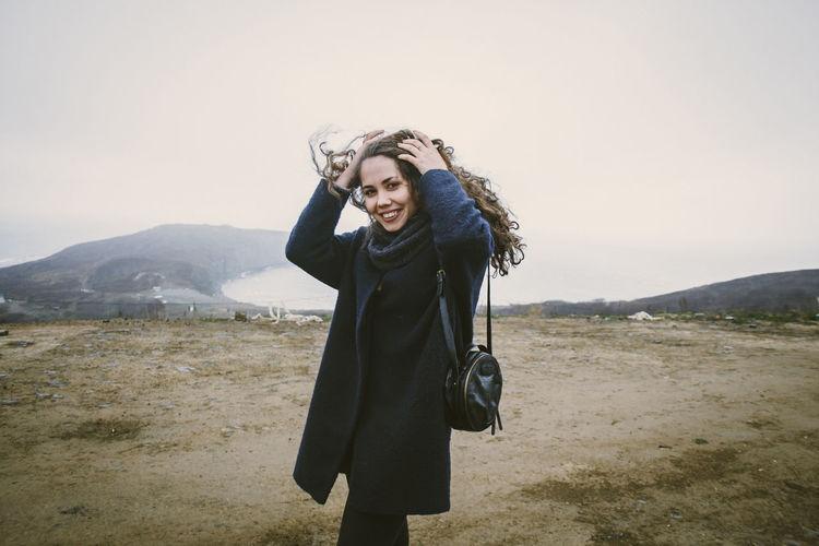 Portrait Of Happy Woman In Coat Standing On Field Against Sky