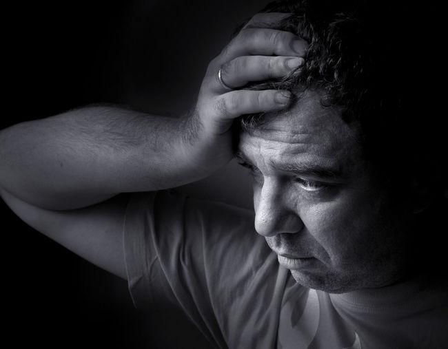Close-up depressed man against black background