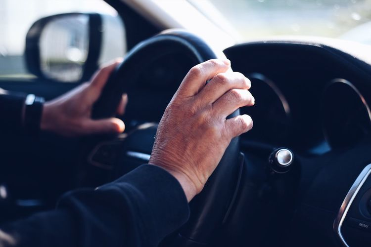 Cropped hands of person driving car