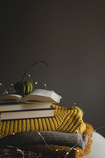 Still life of books, warm clothes and a pumpkin