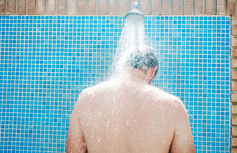 Rear view of man standing by shower outdoors