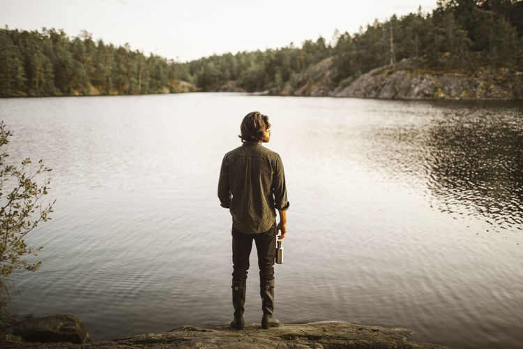 Rear view of man standing on lake