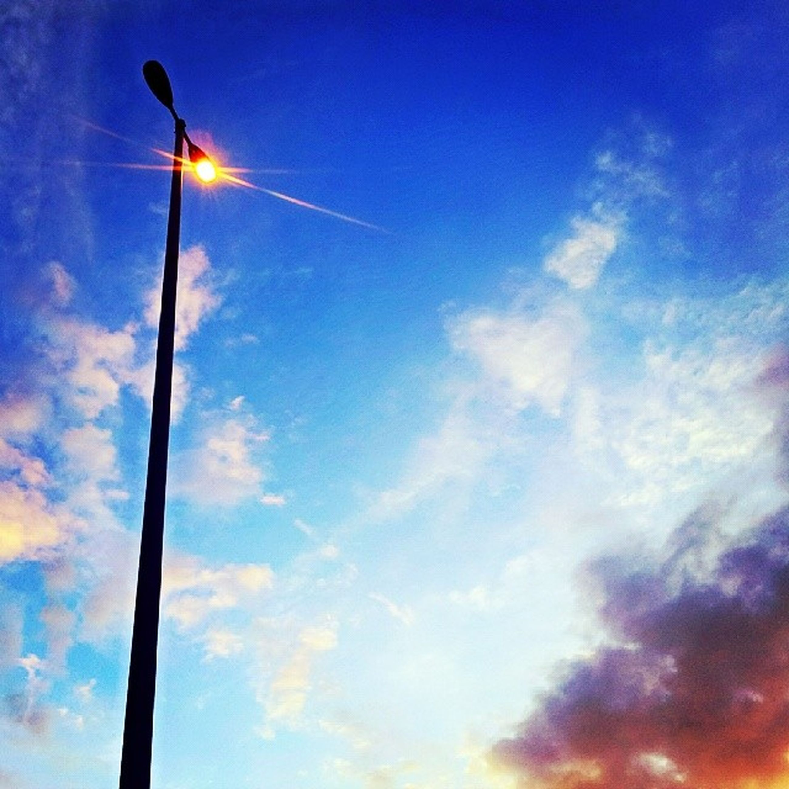 low angle view, street light, sky, lighting equipment, blue, cloud - sky, sun, electricity, pole, tranquility, sunbeam, sunlight, nature, beauty in nature, lens flare, scenics, cloud, vapor trail, outdoors, tranquil scene