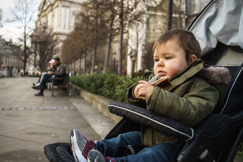 Chewing Sunglasses Babyboy Pushchair Buggy Watching People Baby Stroller Childhood Day Happiness Land Vehicle Lifestyles One Person Outdoors Real People Side View Sitting Transportation Tree Warm Clothing