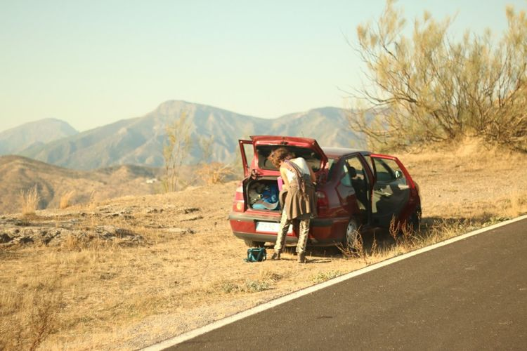 Rear view of woman standing by car on roadside with mountains in background