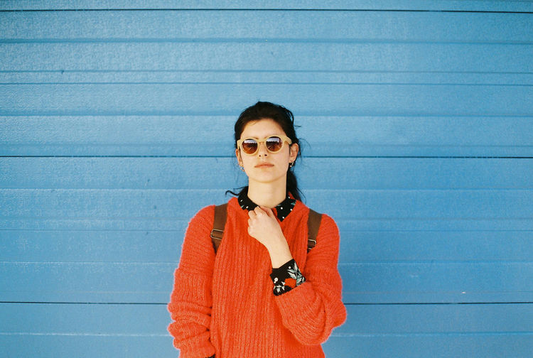 Portrait of woman wearing sunglasses while standing against blue wall