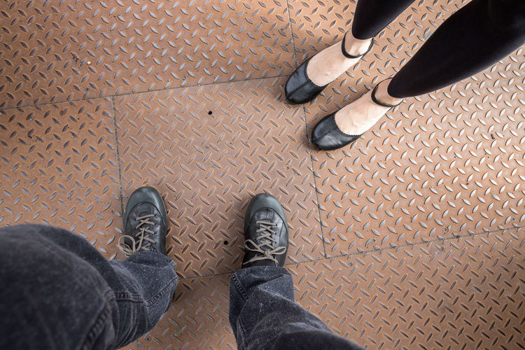 Low section of people standing on diamond plate