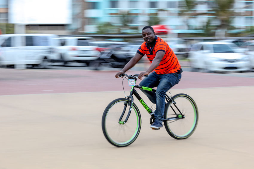 Promenade on Durban beachfront Beach Front Blurred Motion Casual Clothing Cycling Cycling On The Beachfront Durban Exercising Leisure Activity Lifestyles Mode Of Transport Motion Motion Blur On The Move Outdoors Promenade Red Shirt Riding Selective Focus South Africa