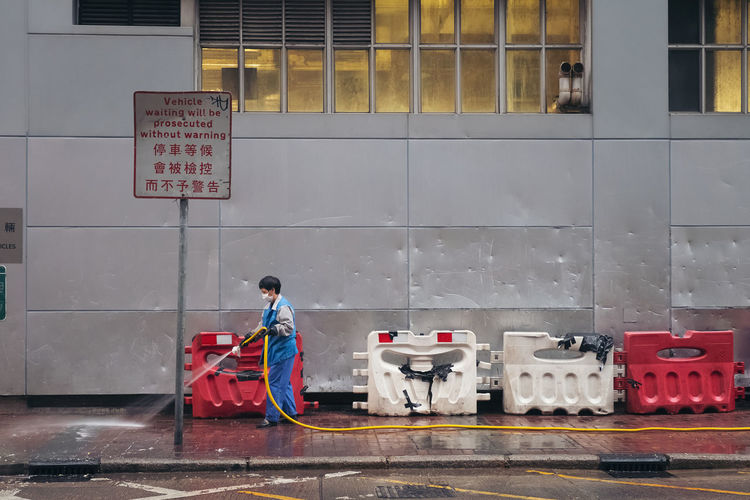 HONG KONG - MAR 09, 2019 : Road sweeper worker cleaning city street and side walk with water in morning on Jordan district in Hong Kong Real People One Person Architecture Full Length Men Occupation Day Built Structure Communication Building Exterior Working Footpath Bag Transportation Cleaning Text Outdoors Walking Container Uniform