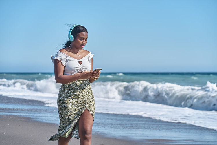 Young african american woman listening to music by the shore of the beach