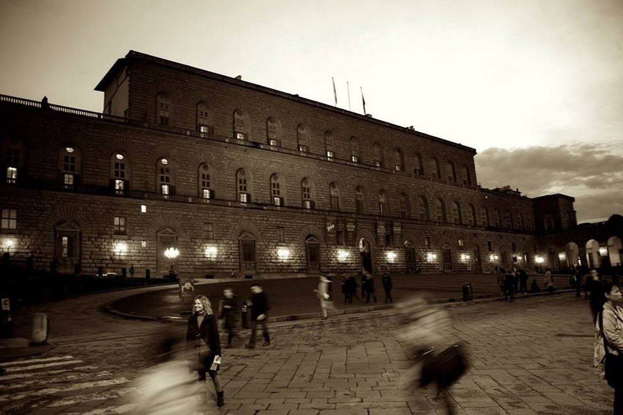 architecture, built structure, building exterior, large group of people, illuminated, real people, night, travel destinations, tourism, walking, town square, history, travel, blurred motion, sky, leisure activity, outdoors, street light, lifestyles, men, women, city, group of people, people, adult, adults only