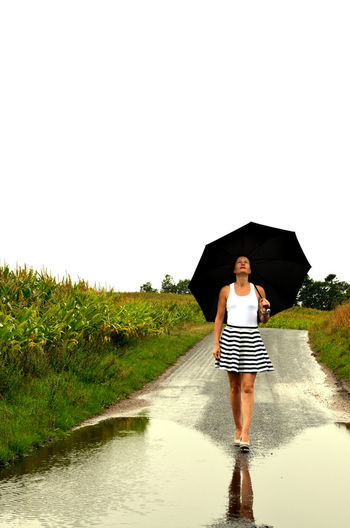 Casual Clothing Clear Sky Copy Space Day Direction Front View Full Length Leisure Activity Lifestyles Nature One Person Outdoors Plant Rain Rainy Season Real People Sky Standing The Way Forward Umbrella Water Women