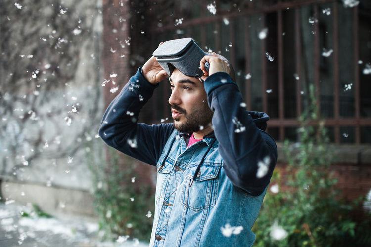 Young man using virtual reality simulator during snowfall
