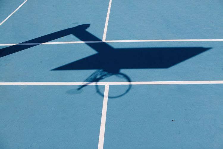 High angle view of basketball hoop shadow on blue court