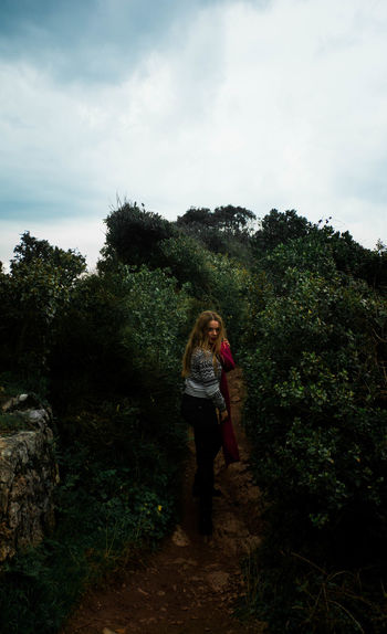 Side view of woman standing amidst plants against cloudy sky