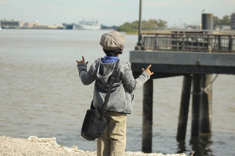 Rear view of boy gesturing while standing at beach