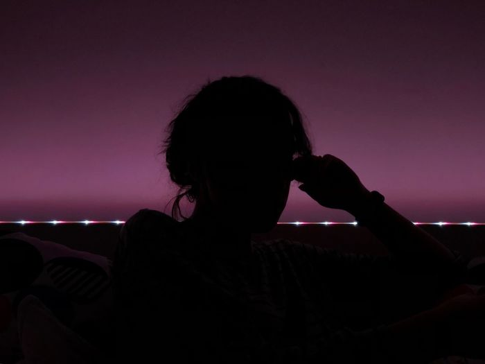 Rear view of silhouette woman against sky during night