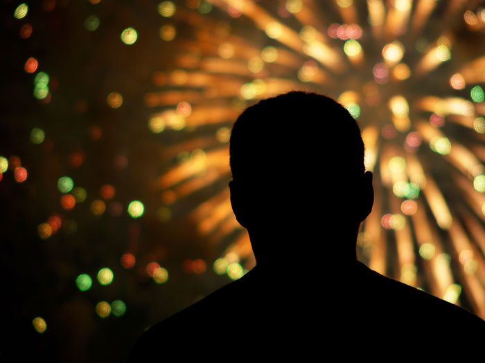 Rear view of silhouette man against firework display at night