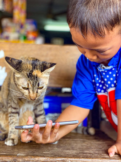 Full length of a boy holding cat