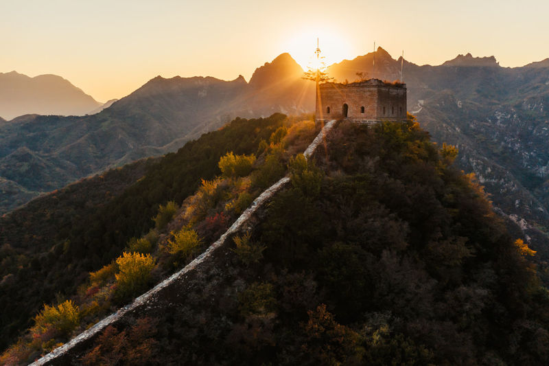 Castle on mountain against sky during sunset