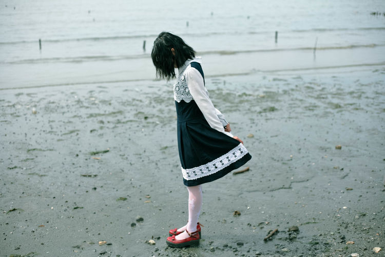 Side view of girl standing on beach