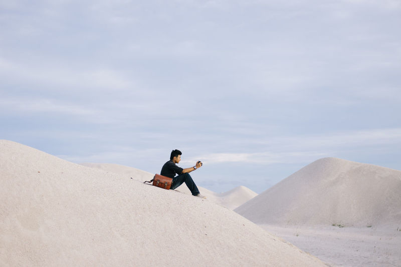 One men having alone time at sand mountain Adult Adults Only Adventure Day Men Mountain Mountain View Mountains One Man Only One Person Only Men Outdoors Sand Sand & Sea Sand Dune Sandboarding Snowboarding Young Adult Welcome Weekly