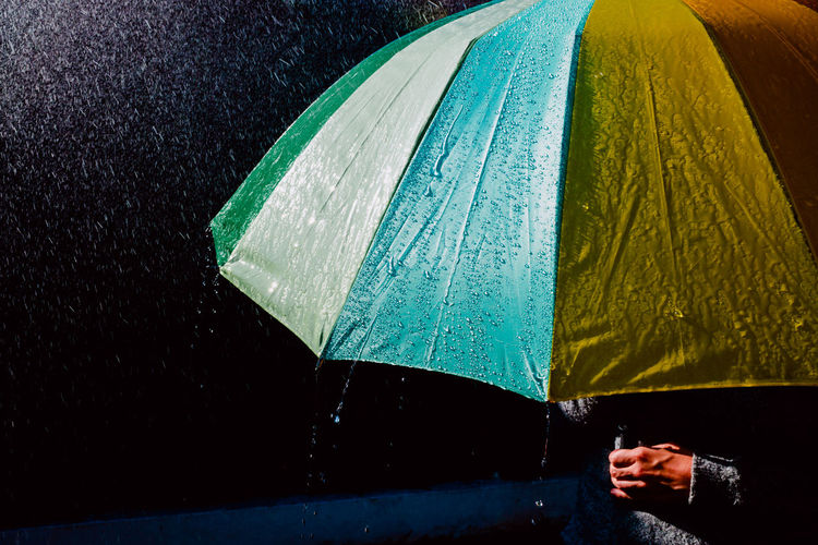 Midsection of person holding umbrella during rain