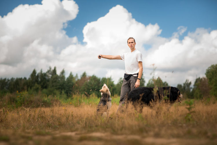 Portrait of young man with dogs on grassy land against sky