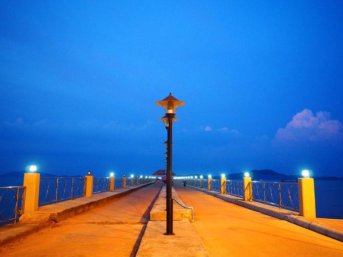 Illuminated street light by sea against sky