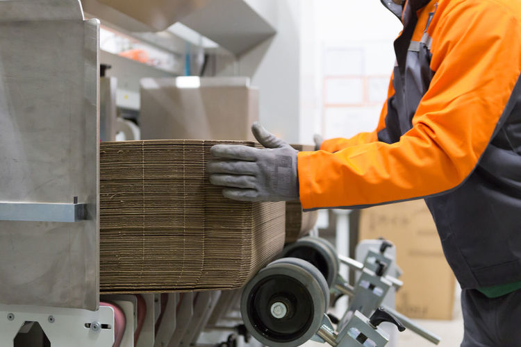 Packaging process, printing and cutting cardboard Occupation Working Real People Protection One Person Industry Protective Workwear Safety Transportation Clothing Men Reflective Clothing Standing Land Vehicle Security Mode Of Transportation Holding Business Uniform Printing Cutting Board Industry Measuring Measurement Factory Horizontal Packaging Industry Cardboard Warehouse Working