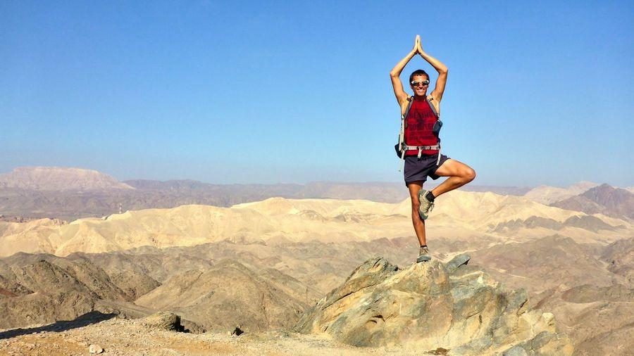 Full length of man doing yoga on landscape against sky
