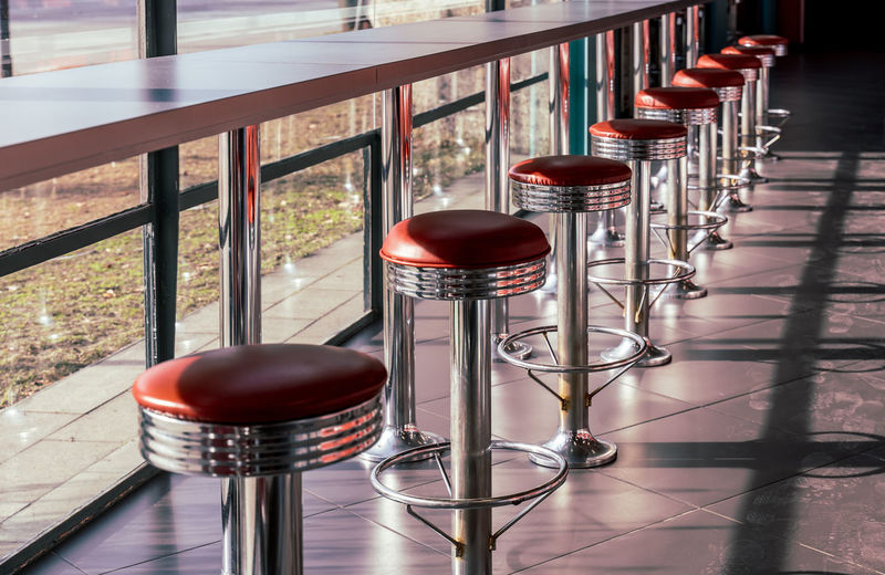 Bar Restaurant Fastfood Barstool Bar Stools Stool In A Row No People Seat Table Indoors  Food And Drink Absence Red Chair Day Empty Metal Railing Drink Glass Refreshment Shadow Flooring Sunlight