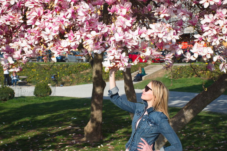 Plant Flower Flowering Plant One Person Tree Beauty In Nature Nature Young Adult Casual Clothing Lifestyles Day Leisure Activity Springtime Growth Hair Human Arm Hairstyle Outdoors Pink Color Fashion Jeans Sunglasses Magnolia Blooming Grass Park Pink