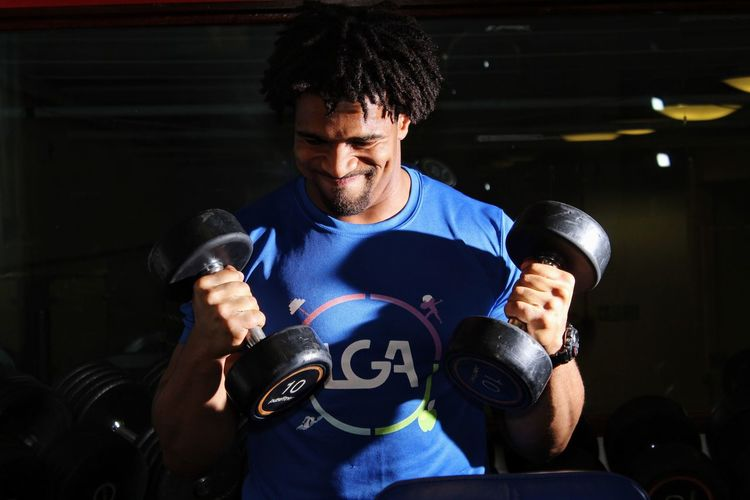 Young Man Lifting Dumbbells In Gym