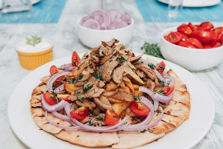 Greek gyros Cuisine Fries Greek Gyros Pork Focus On Foreground Food Food And Drink French Fries Freshness Garnish Meat No People Onions Pita Bread Plate Ready-to-eat Serving Size Sliced Still Life Table Tomato Traditional Tzatziki