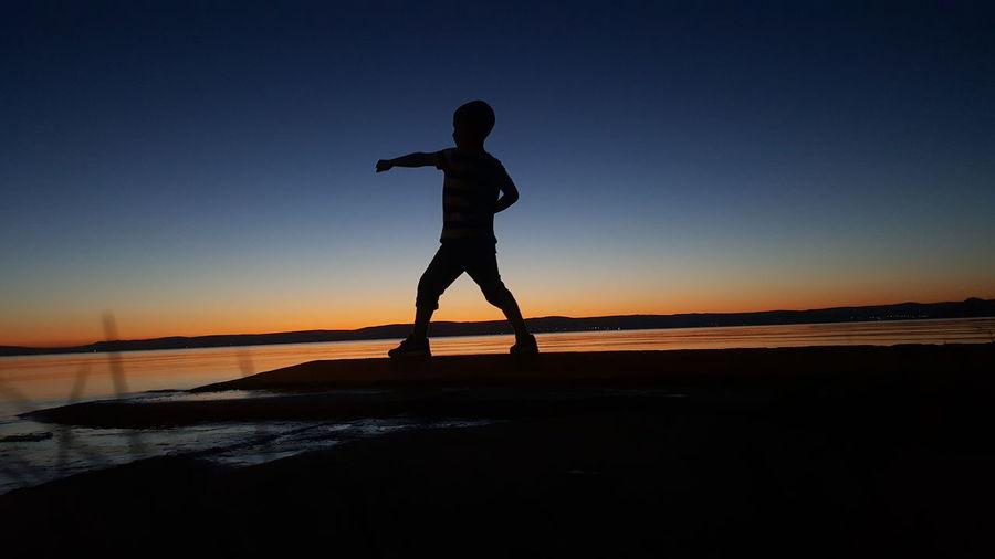 Kid punching air at dusk