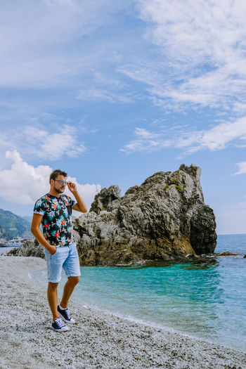 Full length of man standing on rock at beach