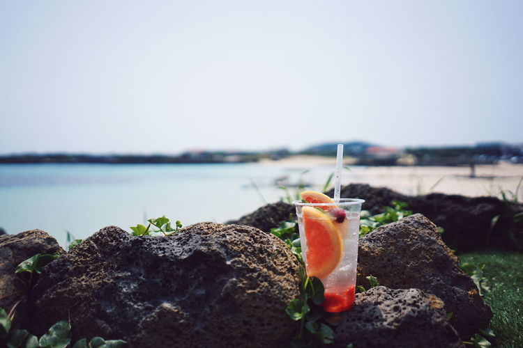 Close-up of mocktail on the rocks by sea against clear sky