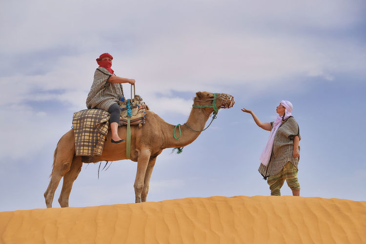 Woman looking at friends sitting on camel in desert
