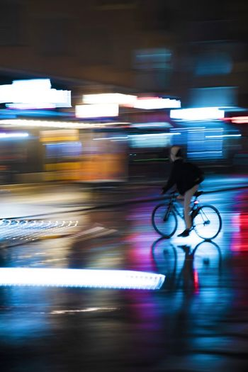 Blurred motion of man riding bicycle on street at night