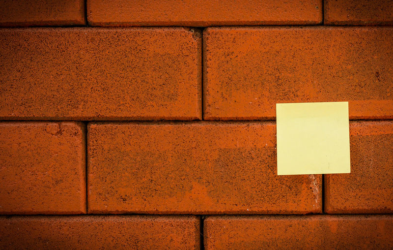 Blank yellow note on brick wall