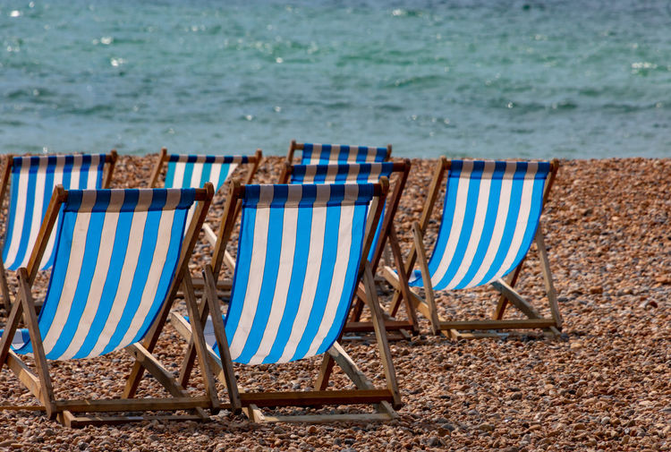 Deckchairs on pebble beach Absence Beach Blue Chair Day Deck Chair Holiday Land Nature No People Outdoor Chair Outdoors Relaxation Sand Sea Seat Striped Travel Destinations Trip Vacations Water