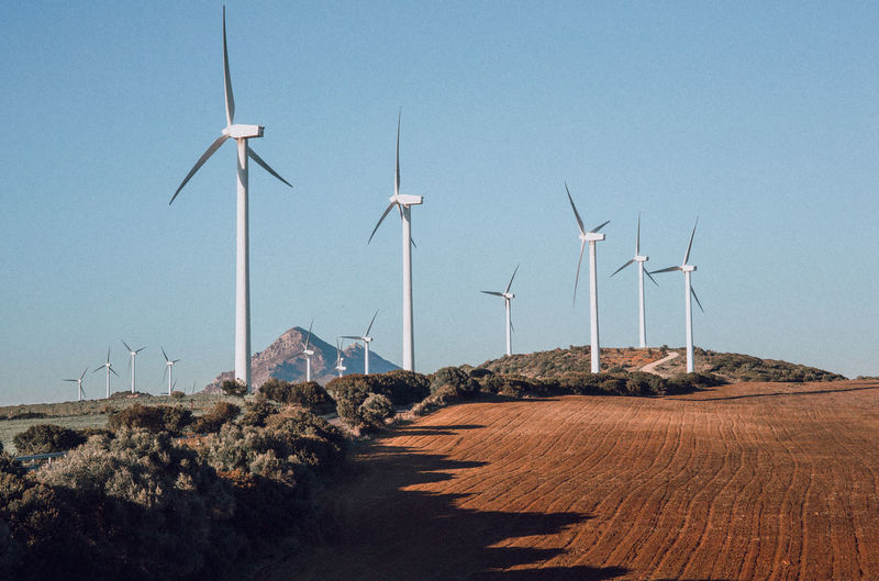 Windmills on landscape against clear blue sky