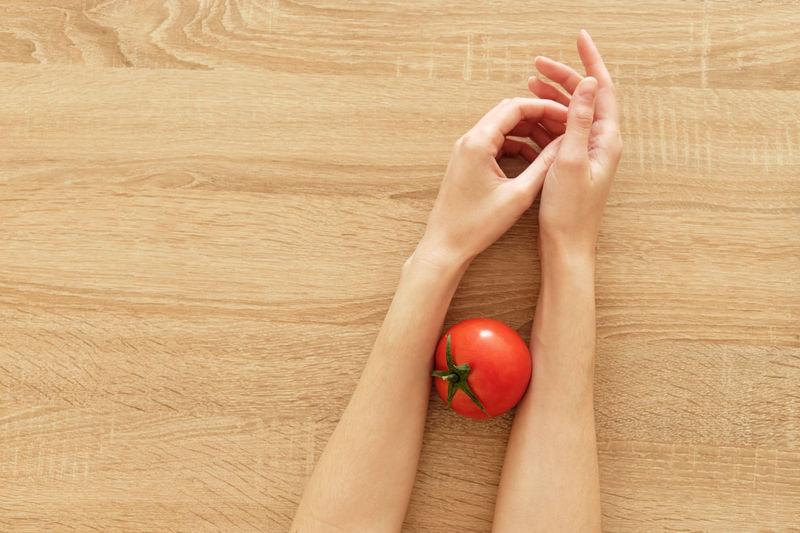 High angle view of hand holding red fruit on hardwood floor