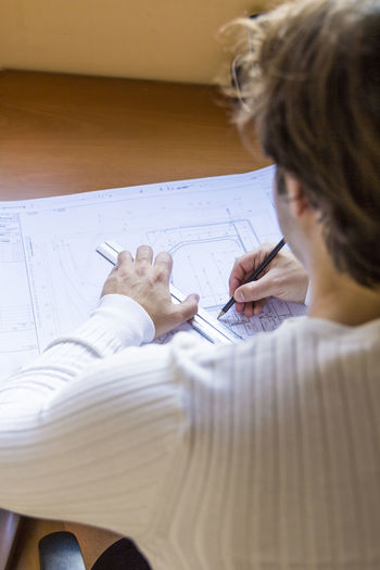 High angle view of architect drawing blueprint at desk