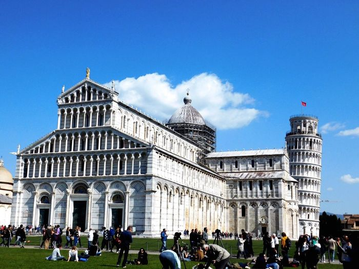 People at piazza dei miracoli against blue sky