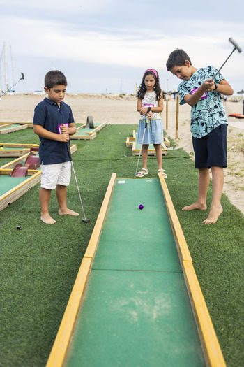 Cute kids playing golf outdoors