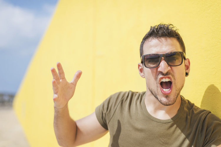 Portrait of man wearing sunglasses shouting while sanding against wall outdoors