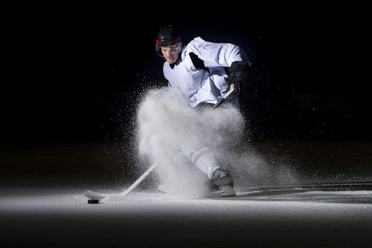 Man playing ice hockey against black background